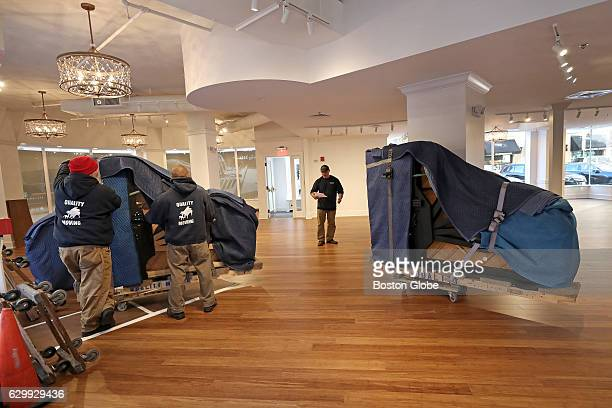 Movers unload a piano at the new temporary home of M Steinert and Sons in the Park Plaza building in Boston on Dec 14 2016 The familyrun piano dealer...