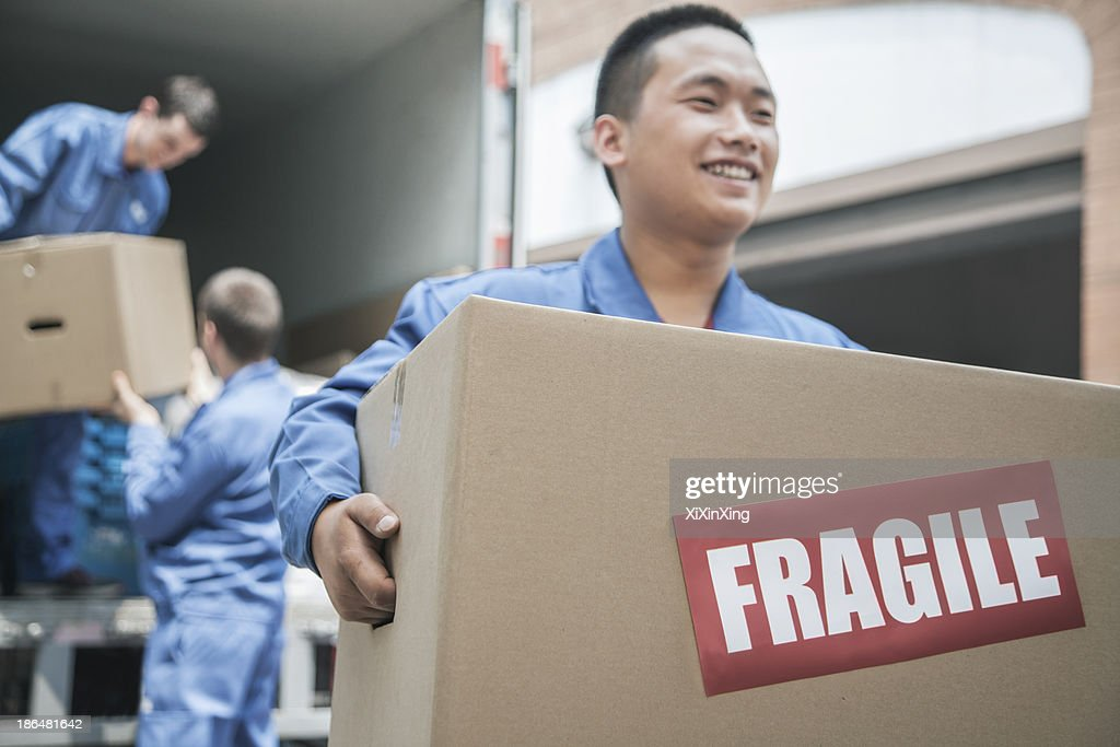 Movers unloading a moving van and carrying a fragile box : Stock Photo