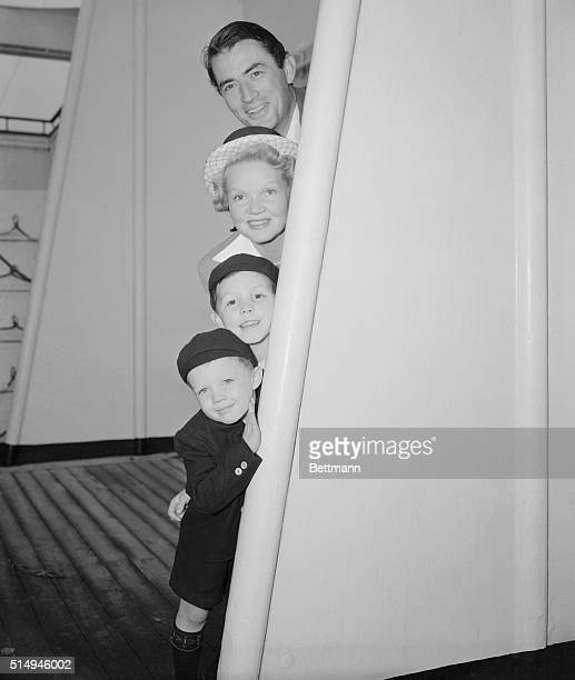 Movie actor Gregory Peck with his wife and children peek at the cameraman aboard the SS Queen Elizabeth at they return from England From top to...