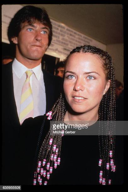 Movie actress Koo Stark is shown here with her hair done in braids Standing behind her is her husband
