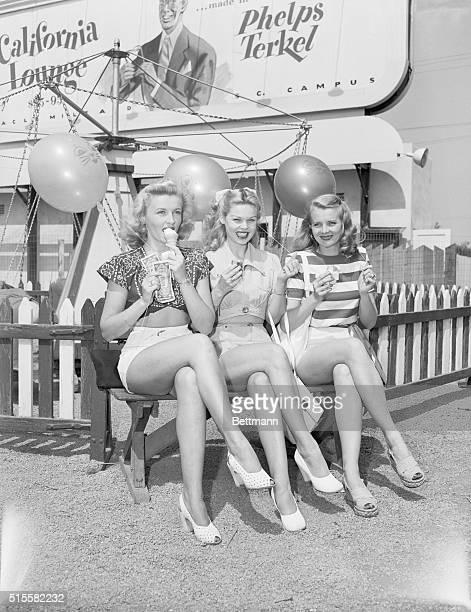 Movie actress Patty Thomas, Sandra Spence, and Dorothy Abbot cool off on a bench in a Santa Monica amusement park.