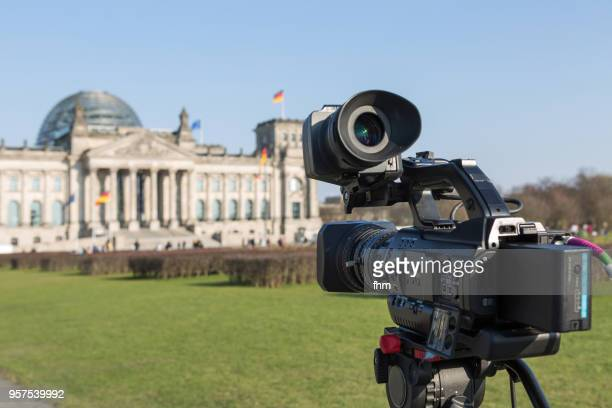 Movie camera with facade of the Reichstag building (german parliament building) - Berlin, Germany