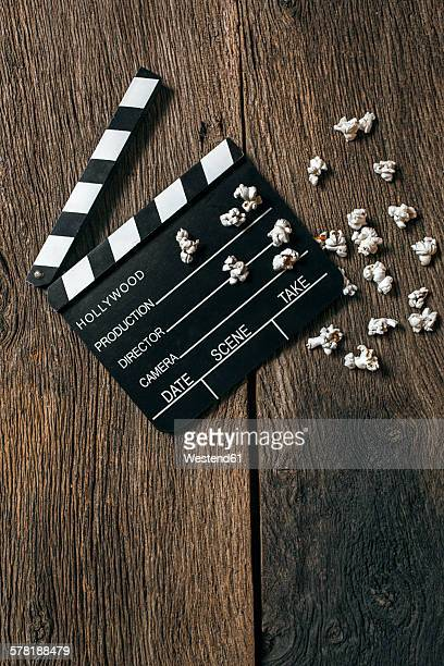 Movie clapper and popcorn on aged wood