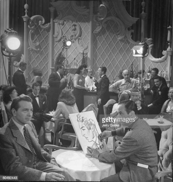 Movie Dir/artist Jean Negulesco drawing a caricature of actor Paul Henreid between takes on the set for his movie The Conspirators at Warner Bros...