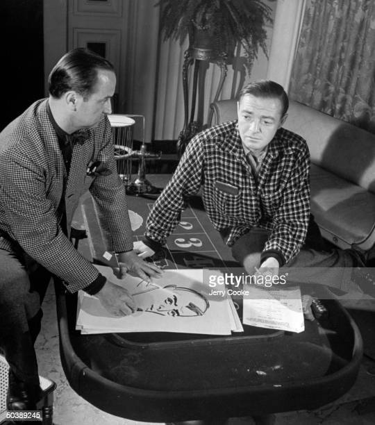 Movie dir/artist Jean Negulesco drawing a caricature of actor Peter Lorre on the Casino gamblling set of his movie The Conspirators during break in...