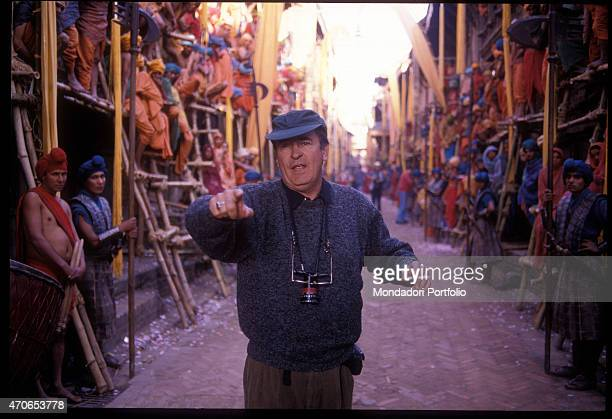 Movie director Bernardo Bertolucci delivers the instructions to the extras on the set for his Little Buddha on 1993 in Kathmandu Nepal