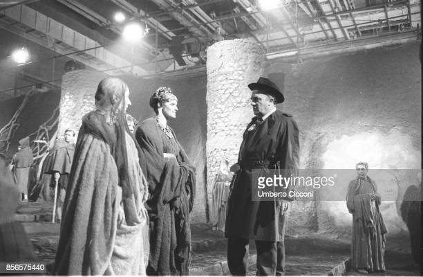 Movie director Federico Fellini talking to two actors while directing the movie 'Satyricon' in 1969