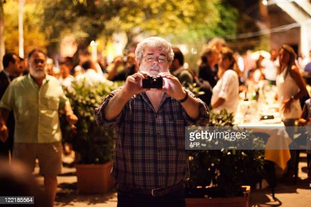 Movie director George Lucas jokes with photographers and takes a photo of them in Bernalda a small city in southern Italy on August 26 2011 the eve...