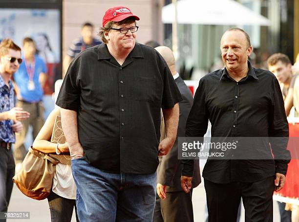 US movie director Michael Moore accompanied by Mirsad Purivatra director of the Sarajevo Film Festival arrives on the red carpet area at the 13th...