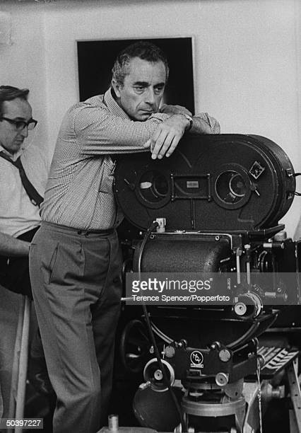 Movie director Michelangelo Antonioni leaning on a camera
