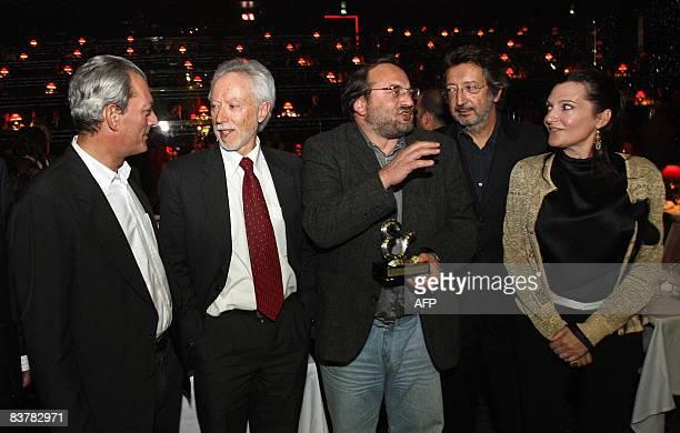 Movie director Mikhail Kalatozishvili of Georgia holds his trophy as he poses with the jury members Paul Auster J M Coetzee Alvaro Sarmento and...