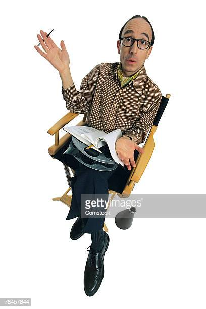 Movie director sitting in chair with quizzical expression