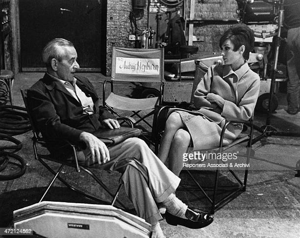Movie director William Wyler amiably talking with Audrey Hepburn both seated on the folding chairs of the film set during the shooting of 'How to...