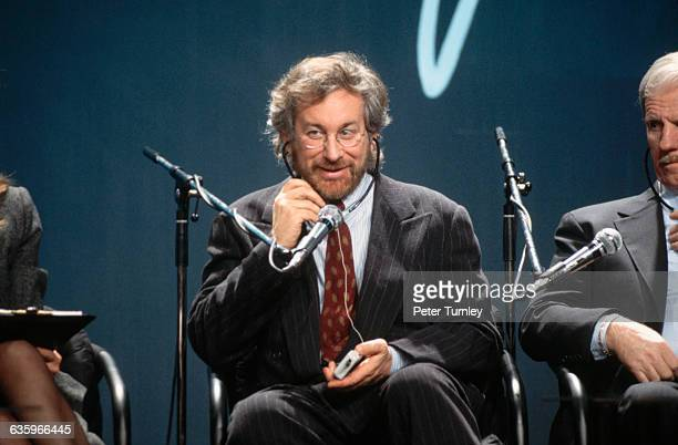 Movie Director/Producer Steven Spielberg plays with the headphones of his real-time translation receiver at the opening of the Polish version of his...