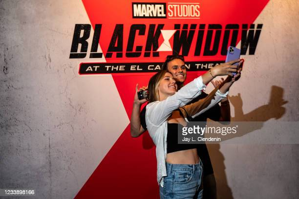 Movie fans take a selfie with a promotional backdrop for Marvel Studios Black Widow, inside the El Capitan Theatre, in the heart of Hollywood, CA,...