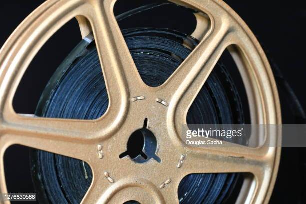 movie film reel on a black background - film stock pictures, royalty-free photos & images