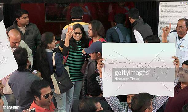 A movie goer films on her mobile during the protest by members of a group asking people to refrain from watching Dilwale movie as part of continuing...