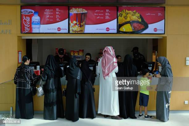 Movie goers buy Cokes and popcorn before watching 'The Incredibles 2' at the newlyopened AMC Cinema in the King Abdullah Financial District on June...