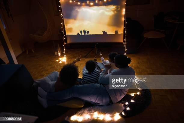 movie night at home! - family watching tv stock pictures, royalty-free photos & images