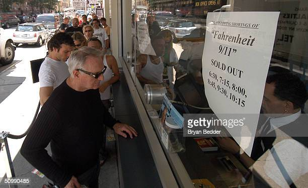 A movie patron buys a ticket at the kiosk of the Loews Village VII theater as a sign indicates all evening showings of 'Fahrenheit 9/11' are sold out...