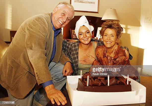 Movie producer Garry Marshall actress/singer Lindsay Lohan and actress Jane Fonda pose with a cake as they celebrate Fonda's birthday on the set of...
