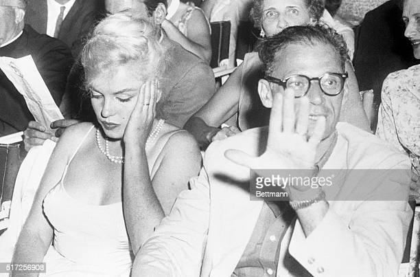 Movie queen Marilyn Monroe wears a bored expression as her playwrighthusband Arthur Miller shoos photographers away at the Boston Arts Center Theatre...