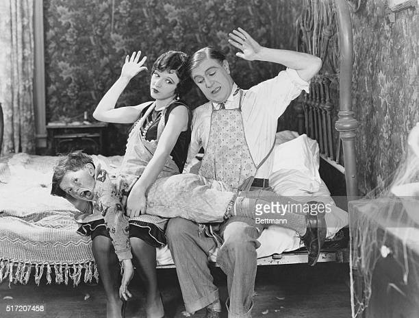 A movie scene featuring actors Wallace Lupino and Betty Boyd as parents spanking their son in the film comedy 'Hard Work' from Educational Pictures...