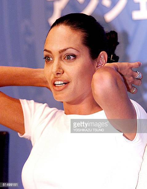 US movie star Angelina Jolie reacts for photographers during a press conference for the promotion of her latest movie 'Tomb Raider' at a Tokyo hotel...