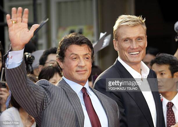 US movie star Sylvester Stallone waves as Swedish actor Dolph Lundgren looks on upon their arrival at a press conefernce for their latest movie 'The...