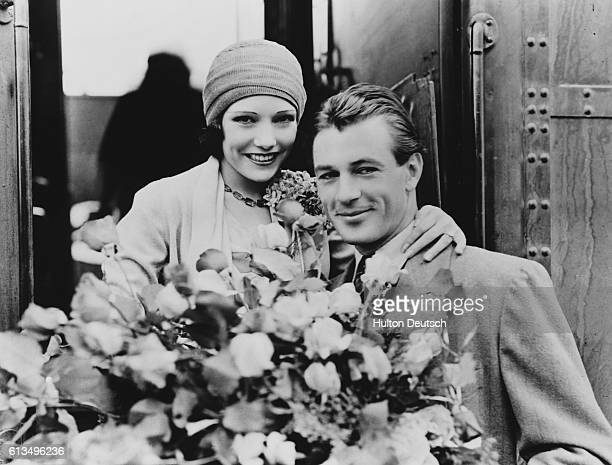 Movie stars Gary Cooper and Lupe Velez dating at the time hold a large bouquet of roses together at a train car in Hollywood