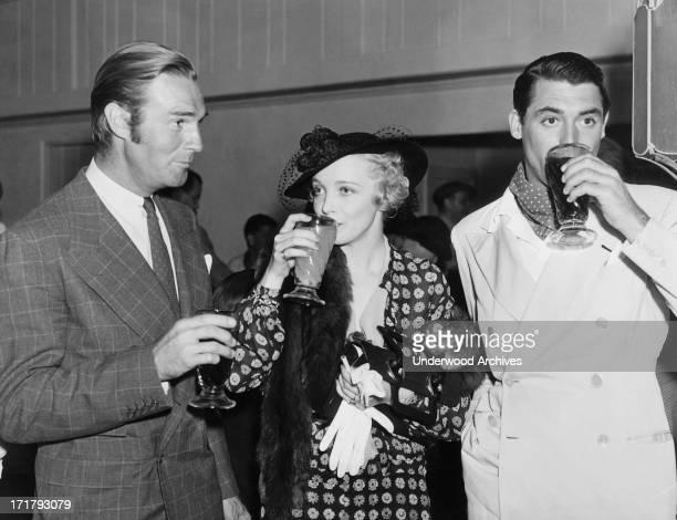 Movie stars Randolph Scott Virginia Bruce and Cary Grant enjoying beverages at a Hollywood event Hollywood California circa 1936