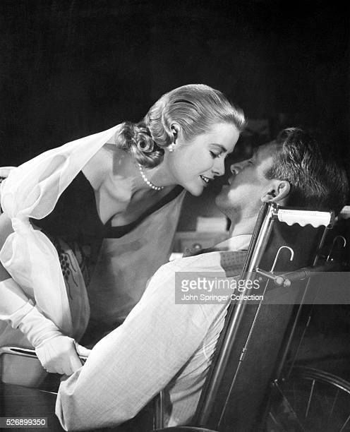 Movie still from Alfred Hitchcock's Rear Window In this sceneJimmy Stewart is sitting in a wheelchair with Grace Kelly leaning in to kiss him