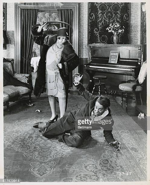 A movie still from the 1928 silent film The Midnight Ace depicting a woman threatening to whip an AfricanAmerican man