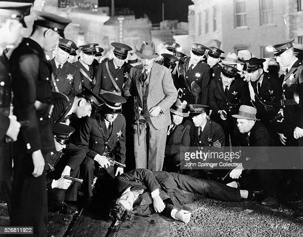 Movie still from the 1932 Howard Hughes gangster film Scarface In this scene a crowd gathers around Paul Muni playing the gunneddown mobster