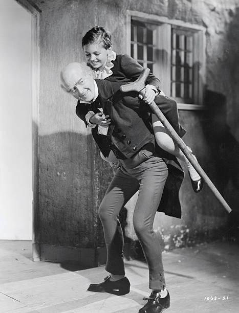 reginald owen carrying terry kilburn on his back - A Christmas Carol Movie 1938