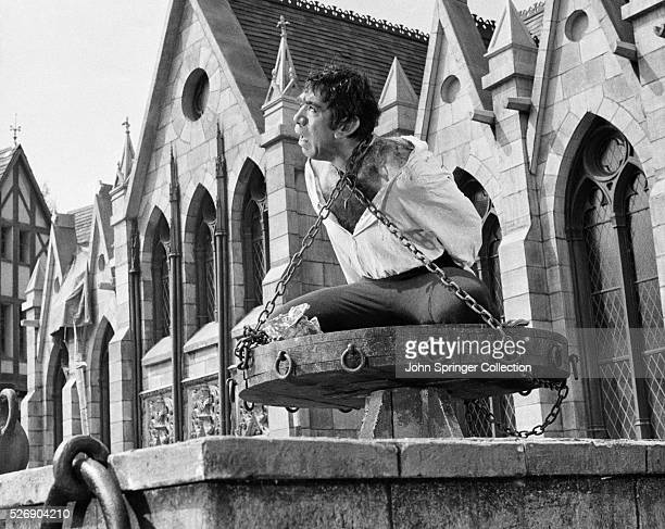 Movie still from the 1957 film adaptation of Victor Hugo's The Hunchback of Notre Dame In this scene Anthony Quinn as Quasimodo is chained atop the...
