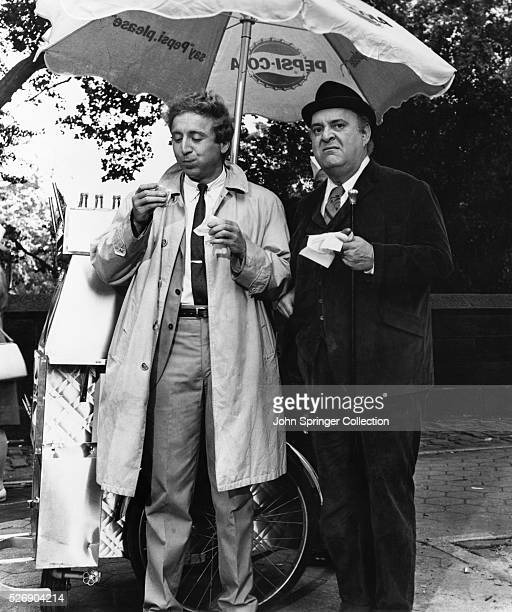 """Movie still from the 1967 Mel Brooks comedy, """"The Producers."""" In this scene, Gene Wilder and Zero Mostel enjoy a hot dog from a vendor."""