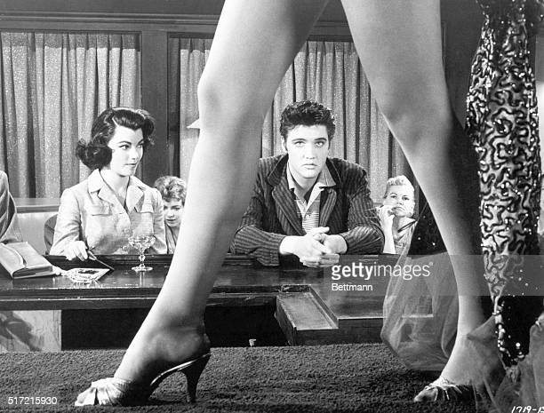 Movie still from the film 'Jailhouse Rock' with Elvis Presley framed within the span of a burlesque dancer's legs as she strides the stage Judy Tyler...