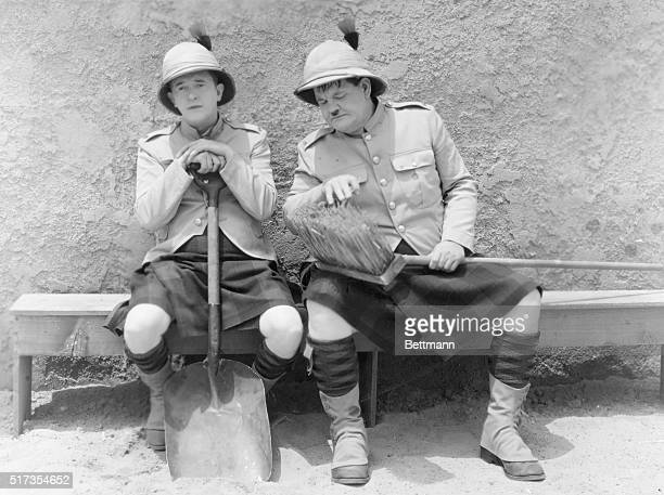 Laurel and Hardy sitting on a bench with British Colonial uniforms on a bench with a shovel and broom