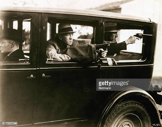 Movie still of two bank robbers firing off rounds from the back of their getaway car One of the men has his Thompson machine gun disguised in a golf...
