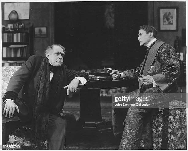Movie still of William Gillette and Ernest Maupin in a 1916 version of 'Sherlock Holmes' In this scene Gillette as Sherlock Holmes points a gun at...
