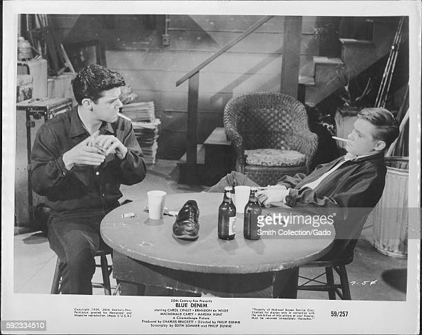 A movie still scene from 'Blue Denim' showing two seated young men with cigarettes in their mouth in serious discussion over two bottles of beer and...