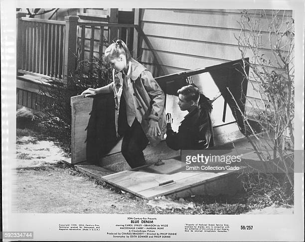 A movie still scene from 'Blue Denim' showing two teenagers a boy and a girl climbing out of a storm cellar with the girl going out first as the boy...