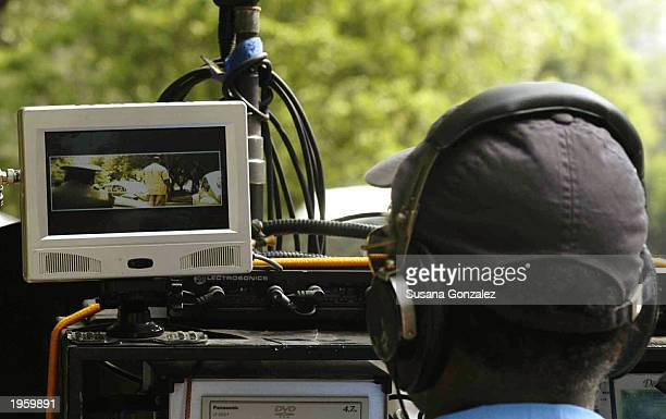 A movie technician watches a scene from the film Man On Fire as it is being filmed on location at Condesa Park April 29 2003 in Mexico City Mexico