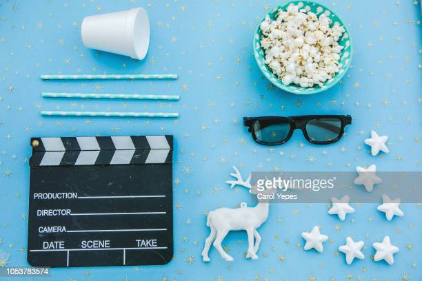 movie tickets, clapperboard, pop corn and 3d glasses in ablue background..flat lay .christmas concept - blue film video stock photos and pictures