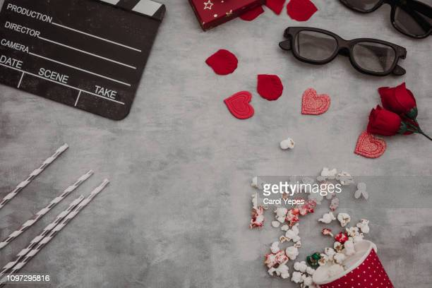 movie tickets, clapperboard, pop corn and 3d glasses in grey.Valentines day concept