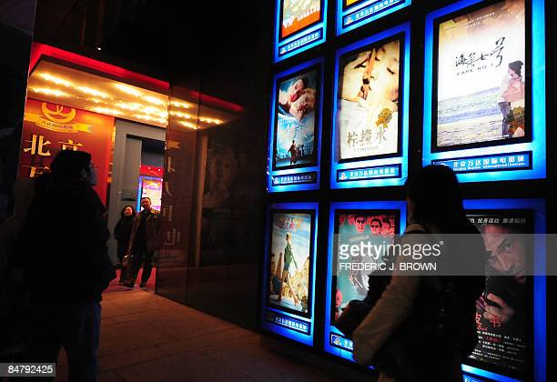 Moviegoers make their way to a multiplex cinema in Beijing on February 14 where the Taiwanese film 'Cape No 7' as advertised on top right hit movie...