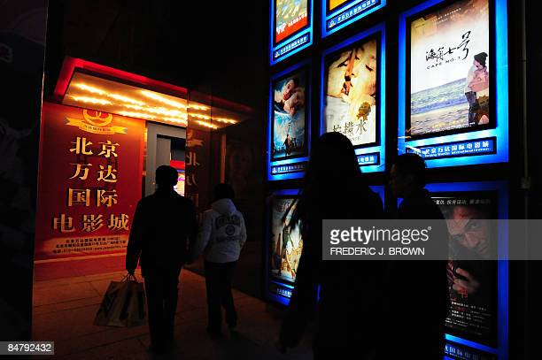 Moviegoers make their way to a multiplex cinema in Beijing on February 14 where Taiwanese film 'Cape No 7' as advertised on top right hit movie...