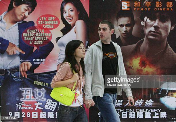 NATIONALITY Moviegoers stand in front of posters advertising Korean and German movies that are currently showing at a cinema in Shanghai 12 October...