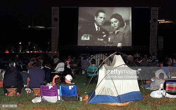 """Moviegoers watch the classic film """"Casablanca"""" on a 20-by-40-foot outdoor screen on the Washington Monument grounds in Washington12 July 1999...."""